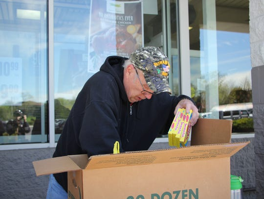 Operation Yellow Ribbon volunteer Tom McElwee stuffs a care package that will be sent from South Jersey to U.S. troops in the Middle East with donations from Rastelli's Market in Marlton, a supporter of the nonprofit group along with other stores like the Ravitz ShopRites.