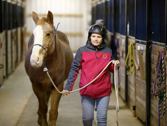 Joyce Leneave , a veteran, takes her horse Shotgun out of the stables at Cincinnati Therapeutic Riding and Horsemanship in Miami Township, Ohio, on Friday, Feb. 2, 2018.