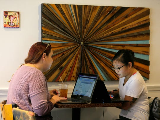Lauren Kloza of Asbury Park and Kelsey Kloza of Ocean Grove, sisters, work on their laptops at America's Cup Coffee Co. in Asbury Park, NJ Friday February 16, 2018. Verizon will bring free Wi-Fi to the shop and others along Cookman and Springwood avenues in exchange for placing nodes - mini cell towers - in town that can eventually handle 5G cellular service.