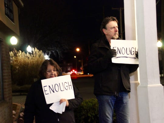 Vickie and Dave Smith from Indivisible Huron Valley hold up signs in support of the Parkland shooting victims.