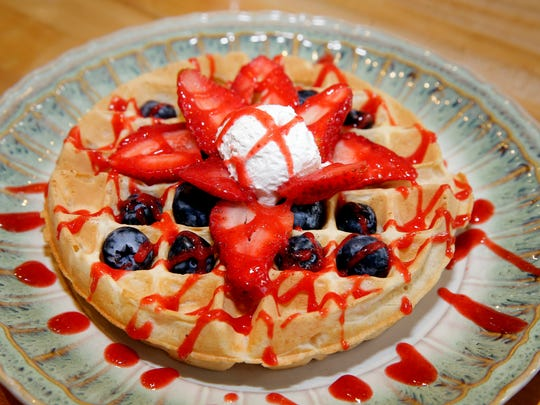 A berry Belgian waffle, made with chickpea liquid in place of eggs, is topped with strawberries, blueberries and coconut whipped cream at On the Bus at the Milwaukee Public Market.