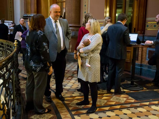 Rep. Megan Jones holds her daughter, Alma Jones, as