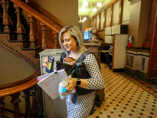 Rep. Megan Jones packs up her daughter, Alma, while talking on a Bluetooth headset on her way to a House Republicans caucus meeting at the Iowa Statehouse on Tuesday, Feb. 20, 2018, in Des Moines. Rep. Jones gave birth to Alma on Jan. 24, 2018.