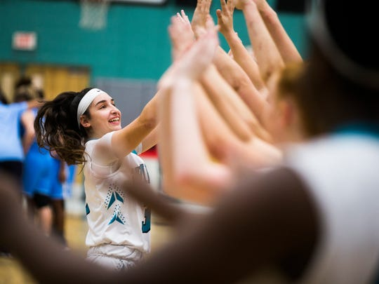 Gulf Coast junior, Mya Giusto, high fives her teammates before the game during the class 8A regional quarterfinal against   North Port High School on Tuesday, February 20, 2018 at Gulf Coast High School.