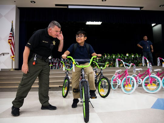 CCSO Sgt. Dan Salls jokingly holds up his hand to hear if Eugenio Arevalo, 9, likes his new bike, which was provided by Mission Love Seeds, at Pinecrest Elementary School in Immokalee on Thursday, Feb. 22, 2018.