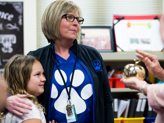 Staci Barretta hugs one of her third-grade students as she receives a Golden Apple award at Big Cypress Elementary in Golden Gate Estates on Friday, Feb. 23, 2018. The Golden Apple awards highlight best practices in teaching and were presented to five teachers in Collier County.