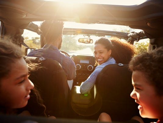 Happy family on a road trip in their car, rear passenger