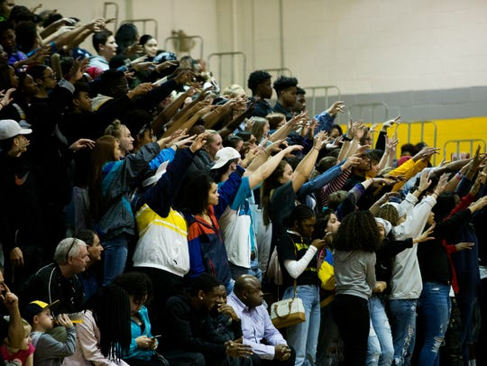 Northeast student fans do the wave during their team's