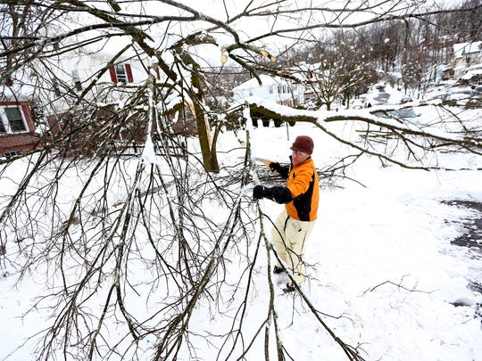 Marshall Keener of Morristown clears a tree away from his driveway that took down power lines on Kenmuir Avenue. About 49,055 Morris County residents woke to no power Thursday morning, the day after a snowstorm walloped the area. With snowfall accumulations close to 2 feet in some Morris County towns, most schools remained closed along with courts and county government offices, except for essential workers. March 8, 2018.  Morristown, NJ.