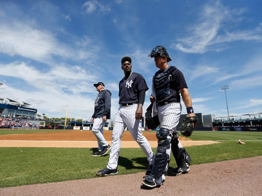 New York Yankees starting pitcher Luis Severino (40), pitching coach Larry Rothschild (58) and catcher Erik Kratz (36) walk to the dugout before the game against the Philadelphia Phillies at George M. Steinbrenner Field.