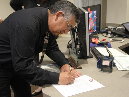 Newly elected Ward 2 city council member Leo Estrada, signs his name after being sworn in Monday, March 12, 2018, at a special ceremony. Estrada was appointed to the seat in 2016.