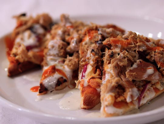 Stilt House is a popular spot for those looking to have full meals or just share a small plate such as the Buffalo chicken flatbread.