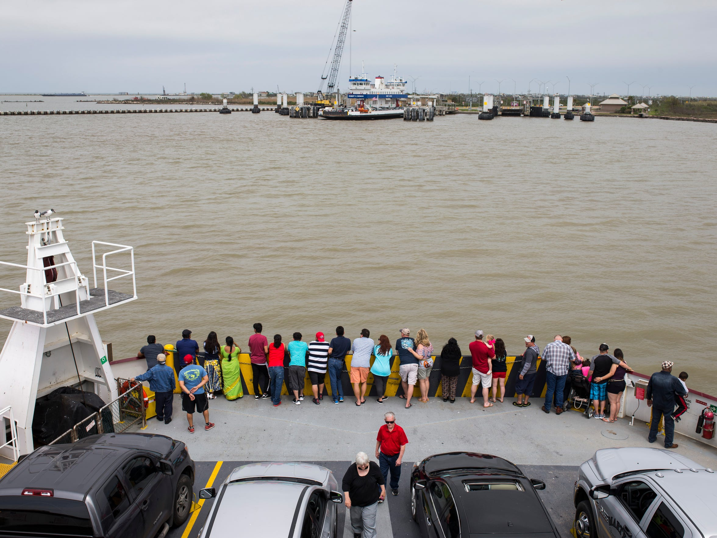 People watch as their ferry approaches Bolivar Peninsula