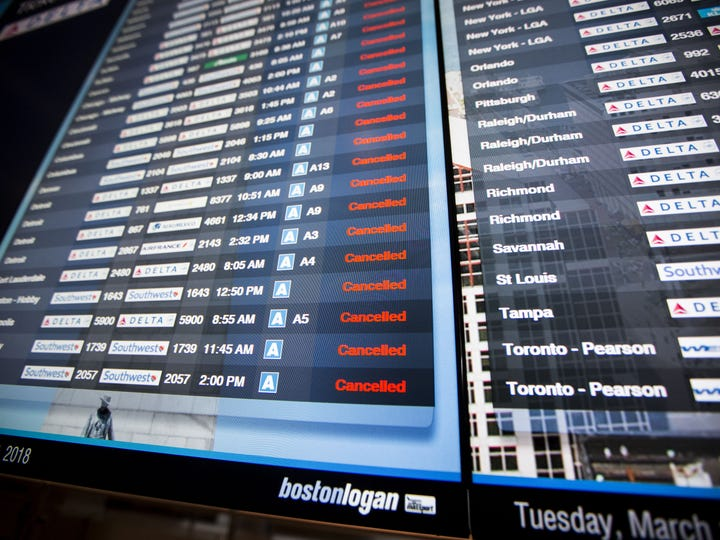 This file photo from March 13, 2018, shows a long list of cancellations on a flight information board at Boston Logan International Airport.