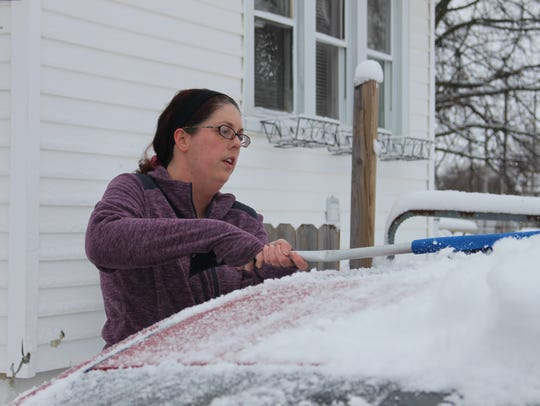 Angela Pickens brushes snow off her car Wednesday.