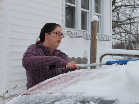 Angela Pickens brushes snow off her car Wednesday. A low pressure system dumped several inches of snow on Marion and the rest of the region overnight.