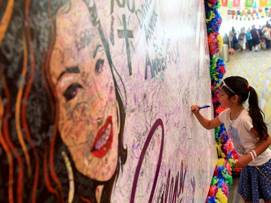 Layla Rangel signs her name on a Selena poster during the second day of Fiesta de la Flor on Saturday, May 7, 2016, in Corpus Christi.
