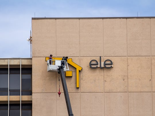 A crew begins to install an Electronic Caregiver sign on the exterior of Las Cruces Tower on Saturday, April 7, 2018.
