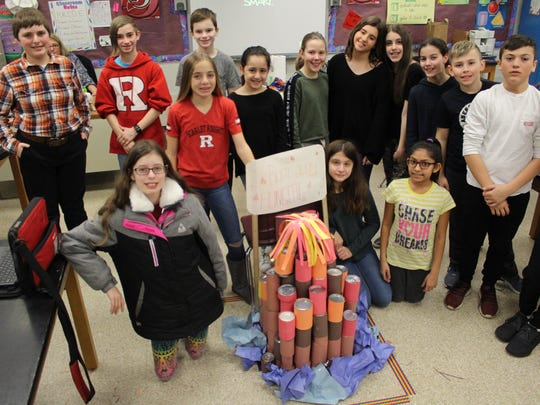 "Sixth-grade students pose with their volcano sculpture, ""Burn away Hunger."" Back row, from left: Matthew Gunn, Aydan Ohlson, Gabriel Kingman, Alexa Walters, Allison Lofling, Gabriella Lobozzo, Madison Landau, Francesca Mannino, Brandon Smulski, David Dubas and Evan Walter. Front row, from left: Miriam Goldstein, Julia Oliveira, Terry DeAngelis and Chelsea Fernandes."