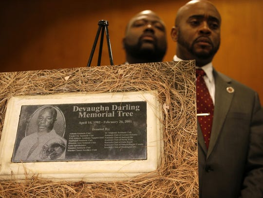 Rep. Alan Williams stands behind a plaque for Devaughn