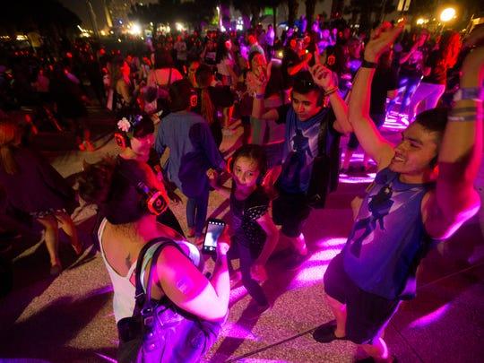 People dance during the silent disco at Fiesta de la