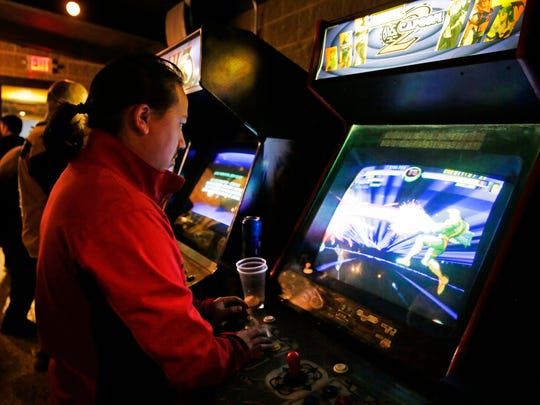 Phong Lor plays a video game during the grand opening of the Player 2 Arcade Bar Thursday, April 12, 2018, on College Avenue in Appleton, Wis.