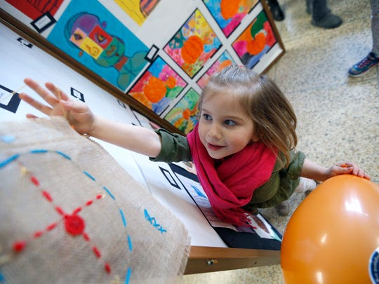 Elizabeth Pennington, 4, of Webster, helps take down and art display from Klem Road North Elementary during the Webster Community Arts Day at Webster Schroeder High School.