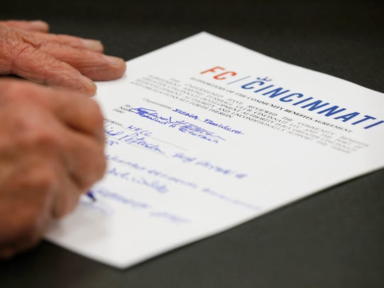Stakeholders sign the new agreement during a press conference to announce a Community Benefits Agreement between FC Cincinnati and the city to support the West End and areas surrounding the proposed soccer stadium at Cincinnati City Hall in downtown on Monday, April 16, 2018.