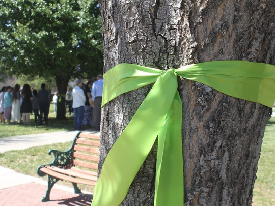 Community members wrapped green ribbons around trees near the Eddy County Courthouse for a vigil for 5-year-old Lucas Hernandez Sunday, April 15. 2018.