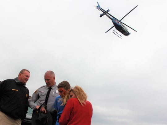 Madison County Sheriff Buddy Harwood and Trooper Mike Weaver of NC Highway show what an arrest of a drunk driver would look like as a medivac helicopter flies away with a crash reenactor inside.