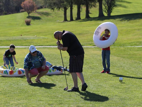Scott Counce, owner of The Merry Wine Market, watches while a golfer tries to hit a marshmallow through an inflatable raft after spinning around his club.