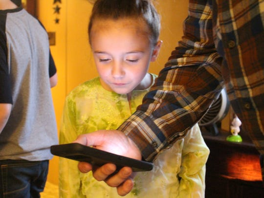 Leieha Gates, 7, looks at pictures of her dad on her
