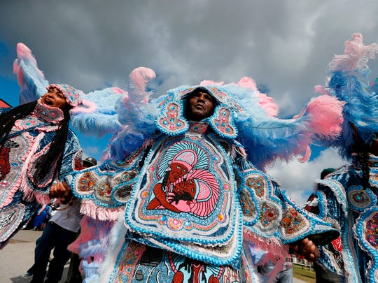FILE - In this file photo, The Cheyenne and 7th Ward Creole Hunters Mardi Gras Indians second line through the crowd at the New Orleans Jazz and Heritage Festival in New Orleans, Thursday, May 4, 2017.  Music lovers are converging this week on the Crescent City for the festival, which takes place over two weekends starting on Friday, April 27, 2018, featuring out-of-town artists such as Rod Stewart and Sting, as well as performers from across New Orleans and Louisiana.  (AP Photo/Gerald Herbert, File)