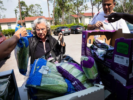 Aida Flores receives fresh lettuce from the Meals of Hope mobile pantry food truck at the YMCA in Naples on Monday, May 1, 2018. They currently distribute healthy and nutritious food, including packed meals, meat, produce and cereal, to families in need at Lely Presbyterian Church every Monday and to families at the Greater Naples YMCA every Tuesday.