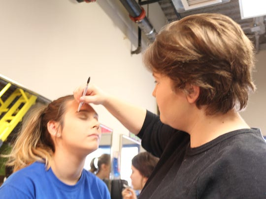 Students apply makeup before Mother of Mercy's final
