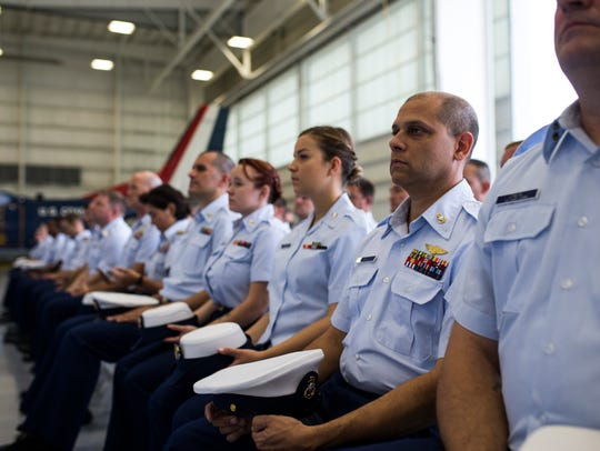 Members of the coast guard listen to speakers during