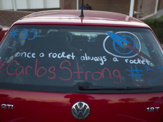 """Messages of support hashtagged """"CarlosStrong"""" sit painted on cars in the lot of Moon Valley High School on October 27, 2017."""