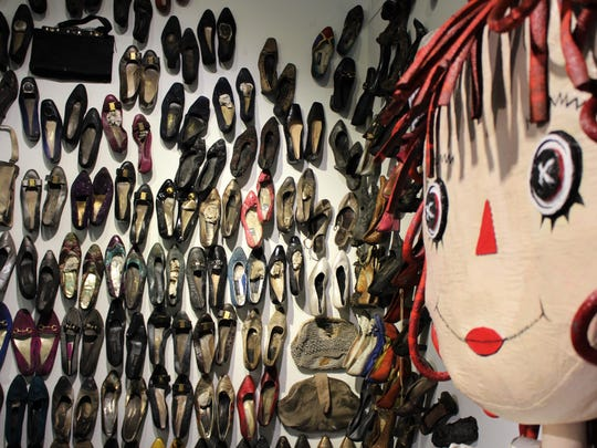 """""""Rags,"""" by Kacy Latham looks over a collection of shoes presented by Cara Hines. The shoes came from Hines' grandmother's house that burned in February 2017. The exhibits are part of the new """"RePlay: Storybook Attic"""" upstairs at The Center for Contemporary Arts."""