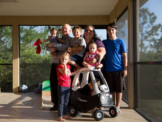 From left, father David Jansen holds one of the foster girls, Lexi 5, Jayden, 5, mother Kara Jansen, holding another foster girl, Noah, 4, and Christopher, 14.