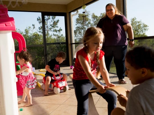 Kara Jansen smiles as she watches over her kids as they play on the family's lanai Monday, May 7, 2018, in rural Collier County. Out of her six children, five are under the age of 6.