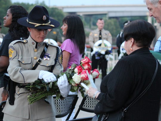 A Rapides Parish Sheriff's deputy hands roses to family members of fallen law enforcement officers.