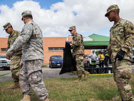 Members of the Army National Guard clean up trash before