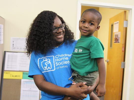 Edna Francois, 31, a dependency case manager supervisor at Children's Home Society, holds 3-year-old Calvin, whose case she oversees. Francois was recognized by CHS for her leadership on Child Welfare Professionals Recognition Day.