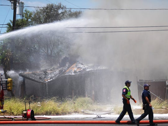 Corpus Christi Fire Department crews battle a building fire Thursday, May 17, 2018, near the intersection of South Port Avenue and Baldwin Boulevard. The Corpus Christi Police Department's bomb squad also responded after firefighters said they found a grenade at the scene.