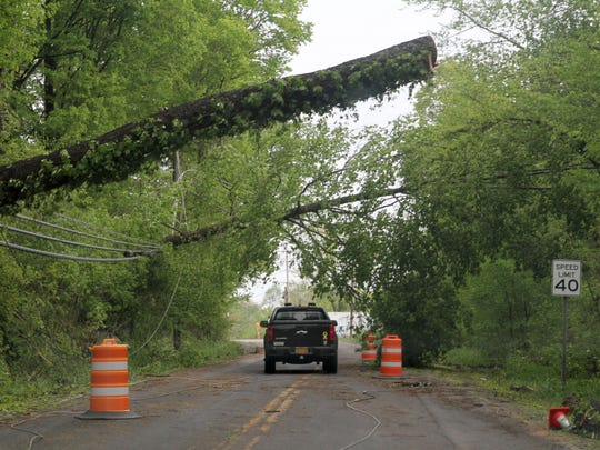 Cars navigate fallen trees and wires along Route 52