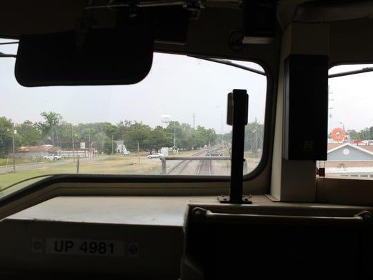 Cars drive through a railroad crossing ahead of a Union