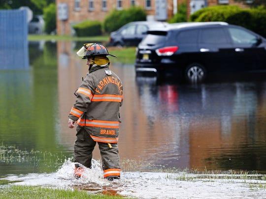Farmingdale  fireman Dustin Brandl negotiates his way through flooded area at Farmingdale Gardens. Farmingdale,NJ Sunday, May 27, 2018 Noah K. Murray-Correspondent Asbury Park Press