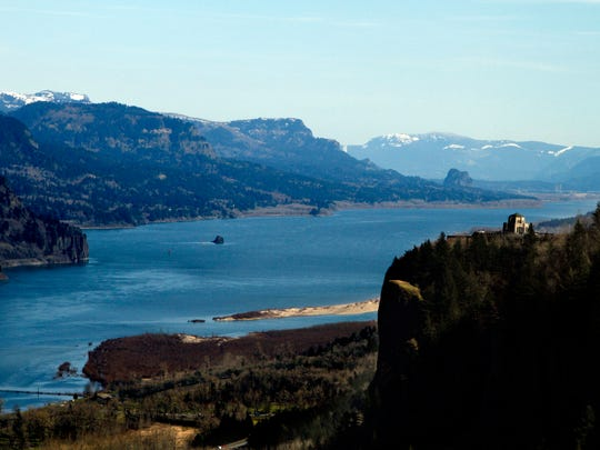FILE - In this March 7, 2012, file photo, the Columbia River flows past the Vista House on Crown Point, right, with Beacon Rock visible in the distance near Corbett, Ore. Talks are scheduled to begin Tuesday, May 29, 2018, in Washington, D.C., to modernize the document that coordinates flood control and hydropower generation in the U.S. and Canada along the Columbia River. (AP Photo/Don Ryan, File)