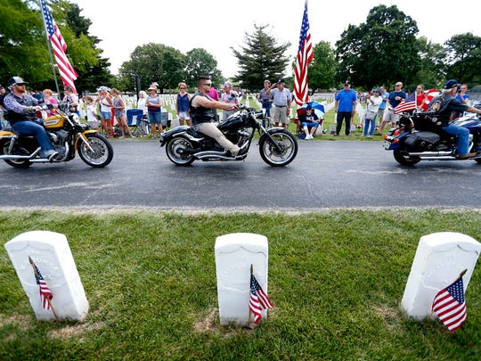 Patriot Guard Riders make an entrance into the Springfield National Cemetery to start a Memorial Day ceremony on Monday, May 28, 2018.