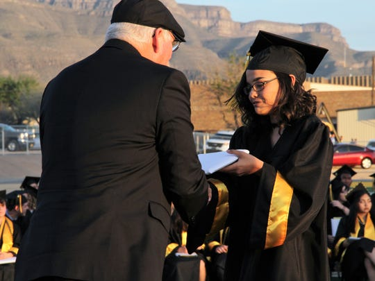 Alamogordo Public Schools Board President David Weaver hands a 2018 graduate her diploma Friday evening.